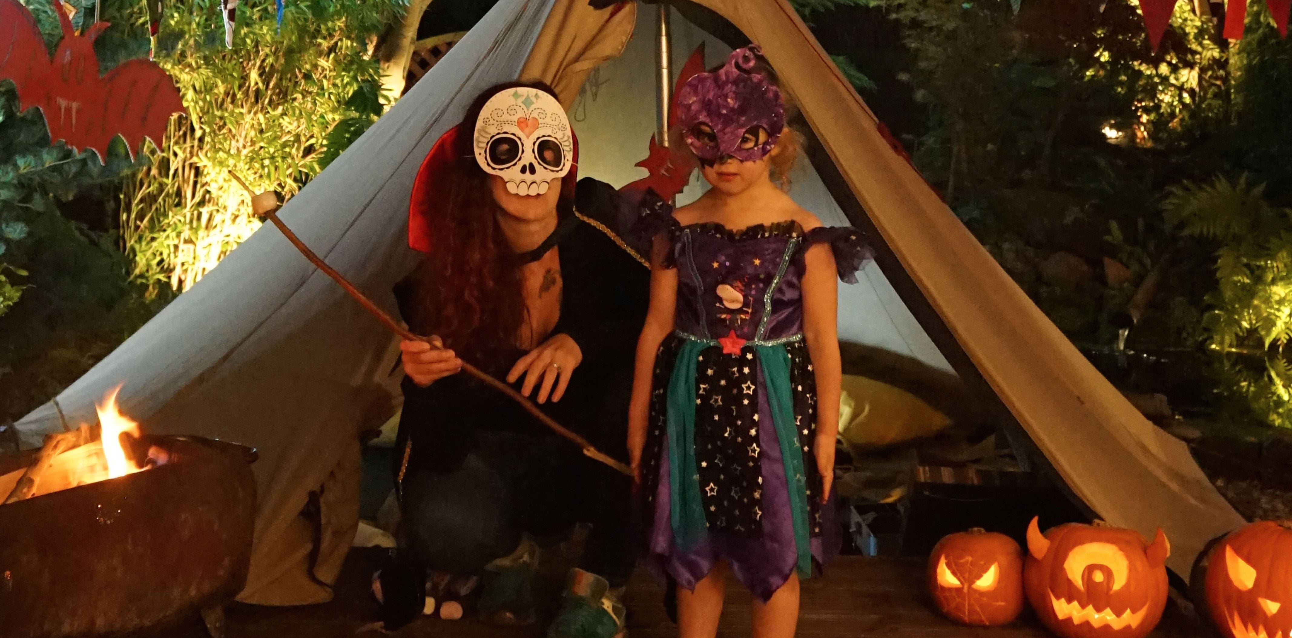 Mother and Daughter stood outside a tent in their backgarden dressed in Halloween costumes